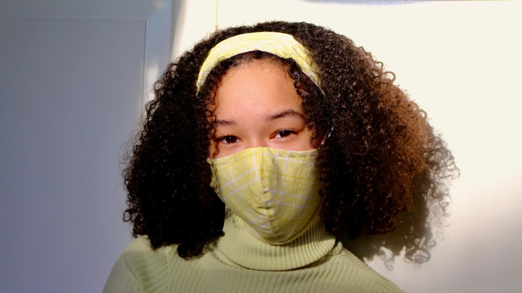 Luv Ya Mask founder Allegra Abrams wearing one of her green fabric masks and a matching headband.