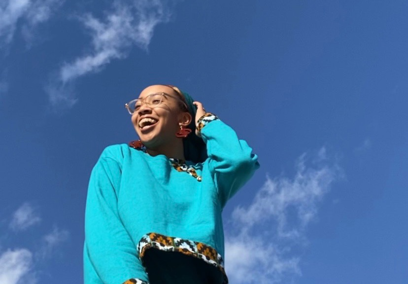 Nzinga Acosta, wearing a turquoise sweater and skirt in front of a blue sky dotted with clouds.